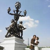 Fotografie African couple hugging next to statue in Paris