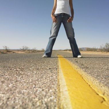 Surface shot of woman standing in middle of deserted road