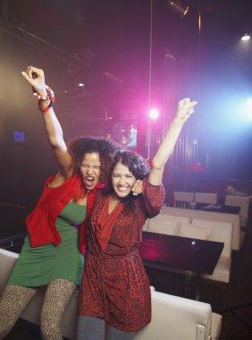 Hispanic women cheering at nightclub