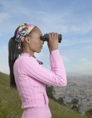 African woman using binoculars over city