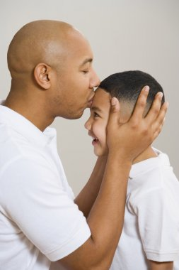 Indian father kissing son's forehead