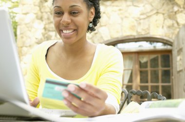 Woman ordering online with credit card and laptop