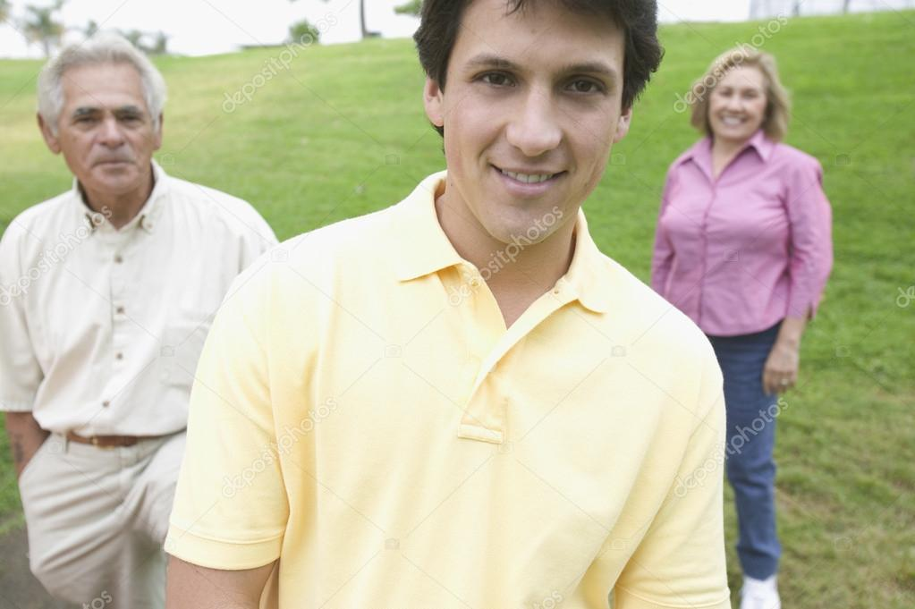 Grown son posing with parents in a park
