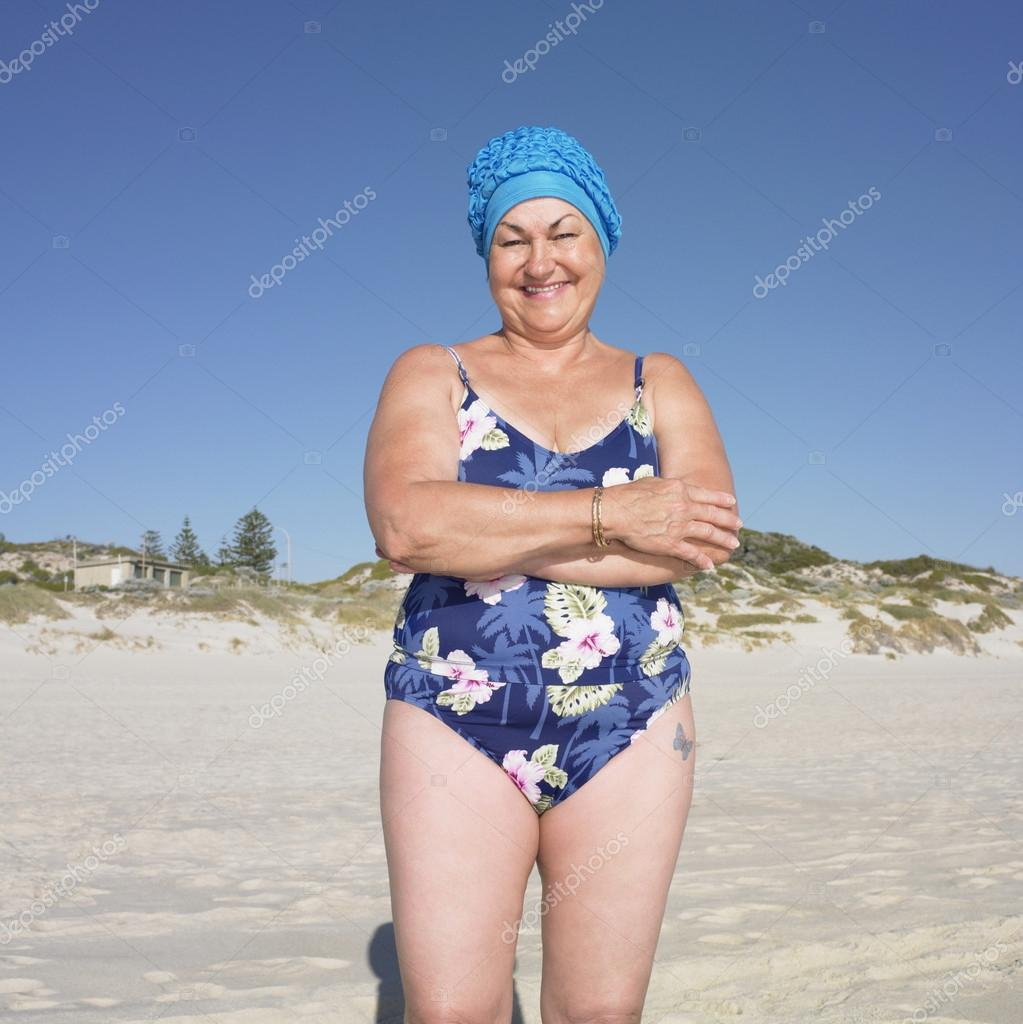 Senior woman in bathing suit smiling at beach