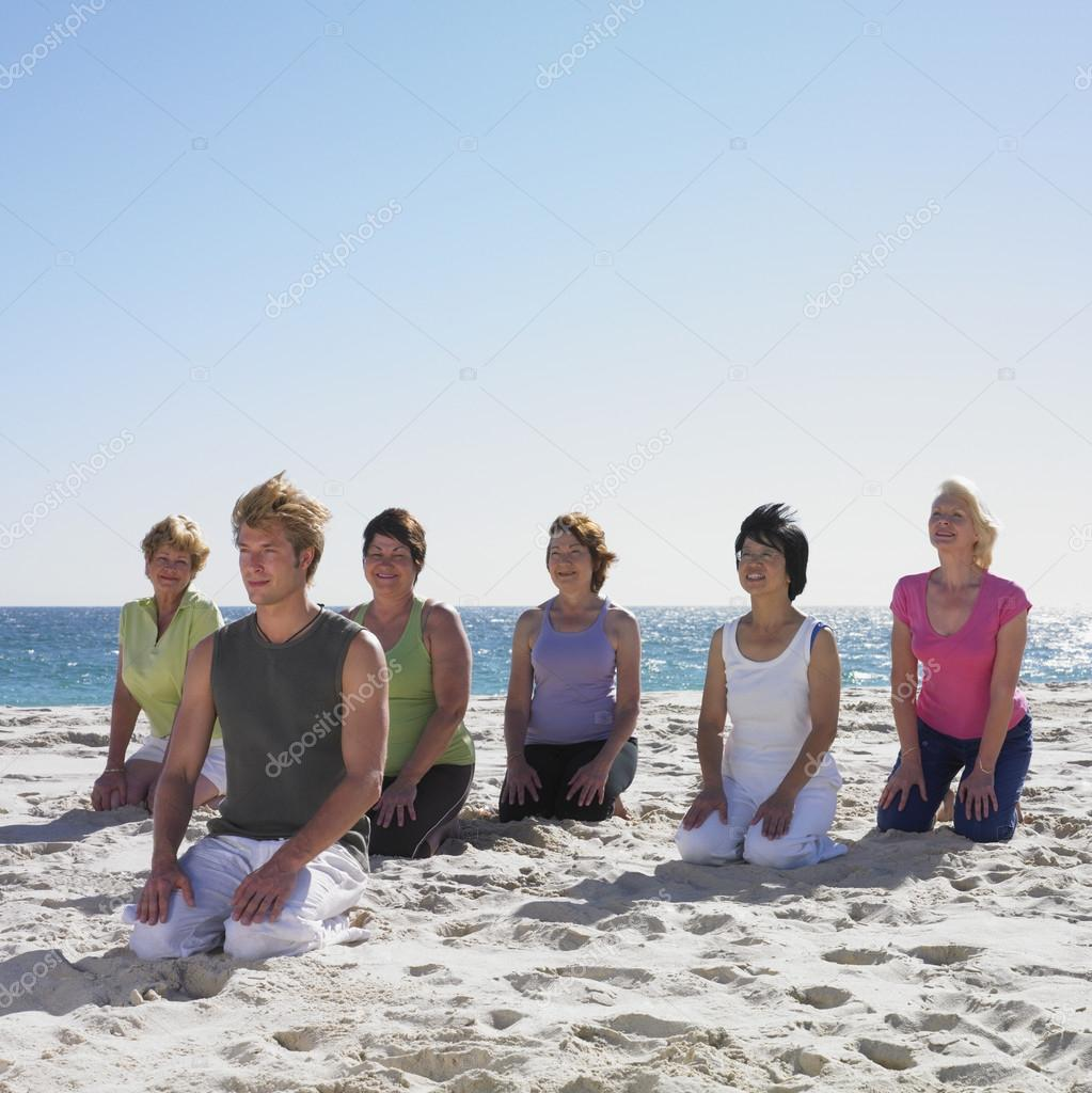 Group of women practicing yoga with instructor on beach
