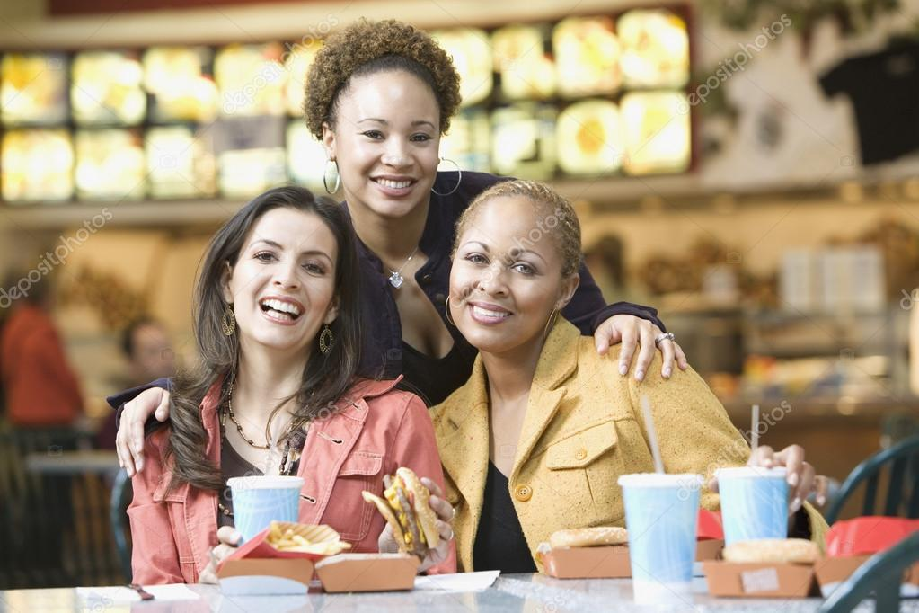 Multi-ethnic women eating in mall
