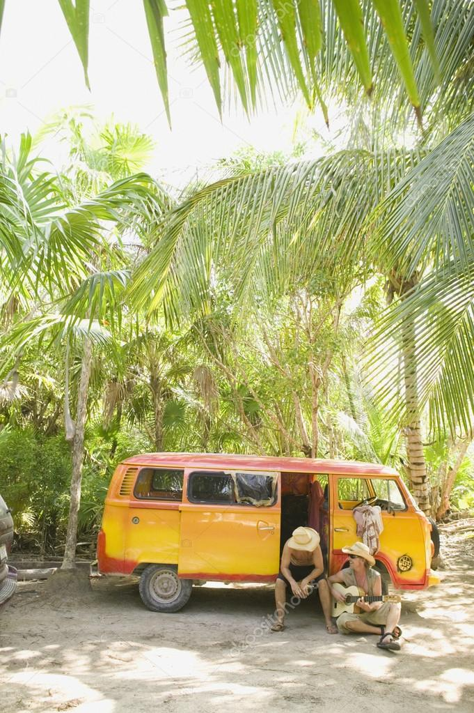sitting with van in tropical setting