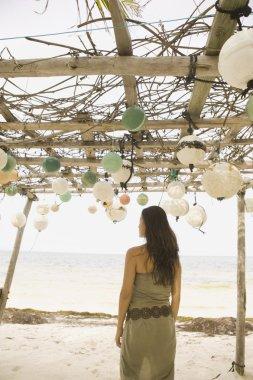 Woman standing beneath awning on beach