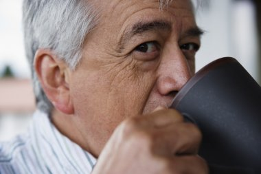 Close up profile of elderly man drinking coffee