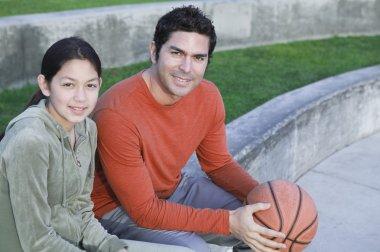 Hispanic father and daughter with basketball