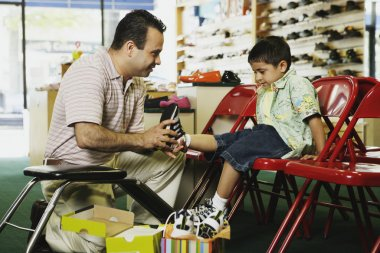 Young Hispanic boy trying shoes at shoe store