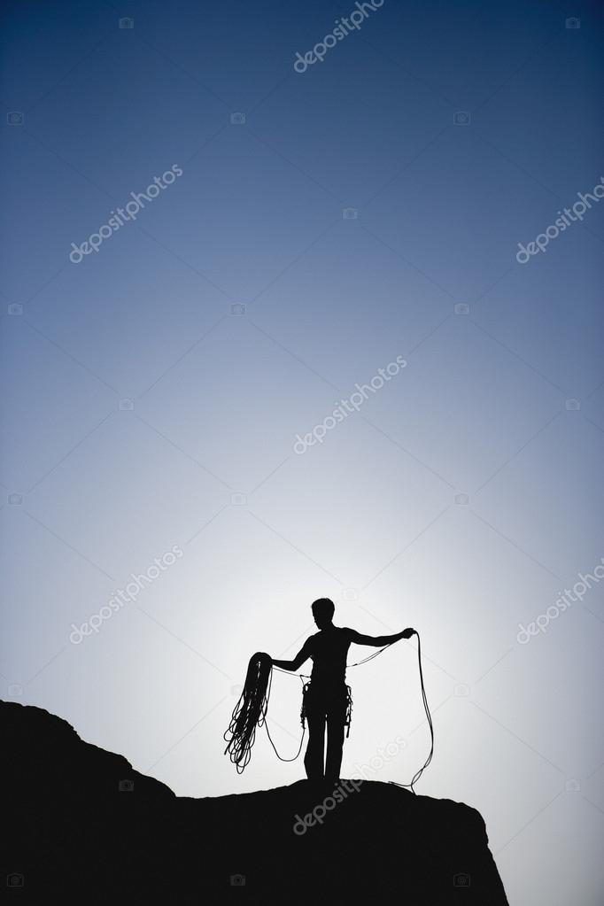 Silhouette of rock climber with rope on mountain