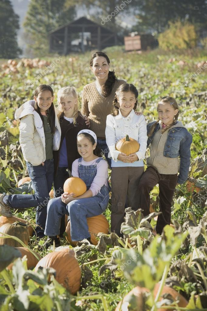 Hispanic woman with group of children in pumpkin patch