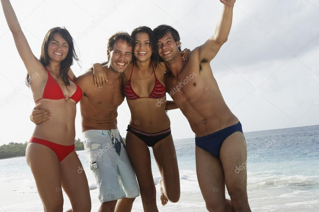 South American couples hugging at beach