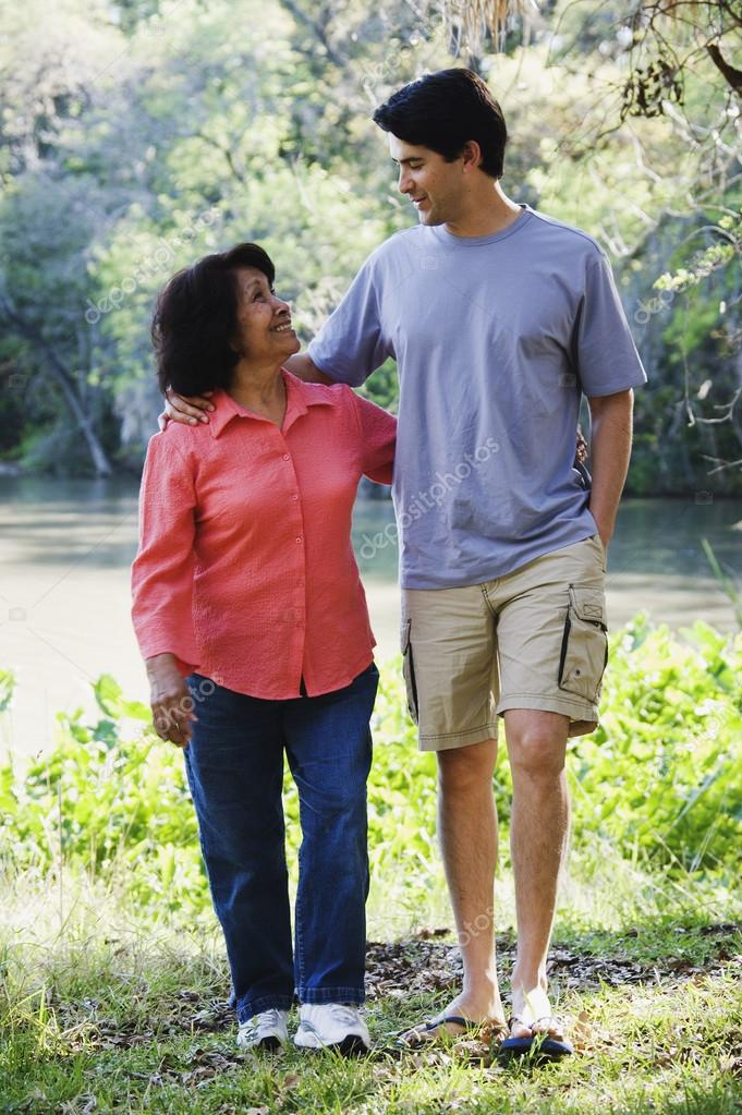 Hispanic mother and adult son walking outdoors