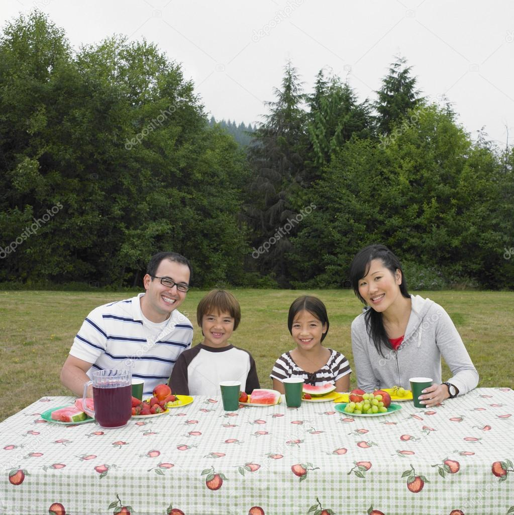 Portrait of multi-ethnic family eating at picnic table