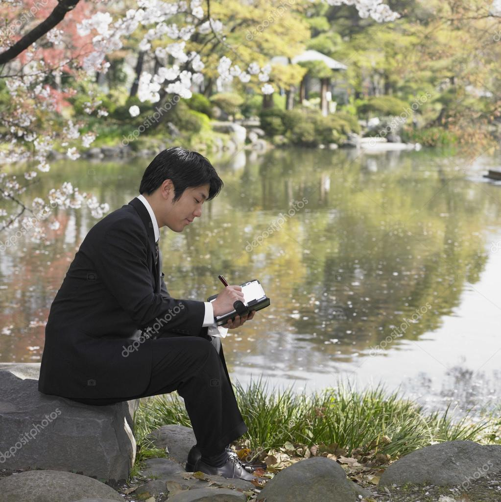 Asian businessman writing in day planner at park
