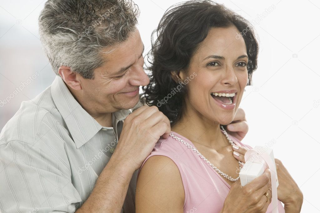 Man giving necklace to woman