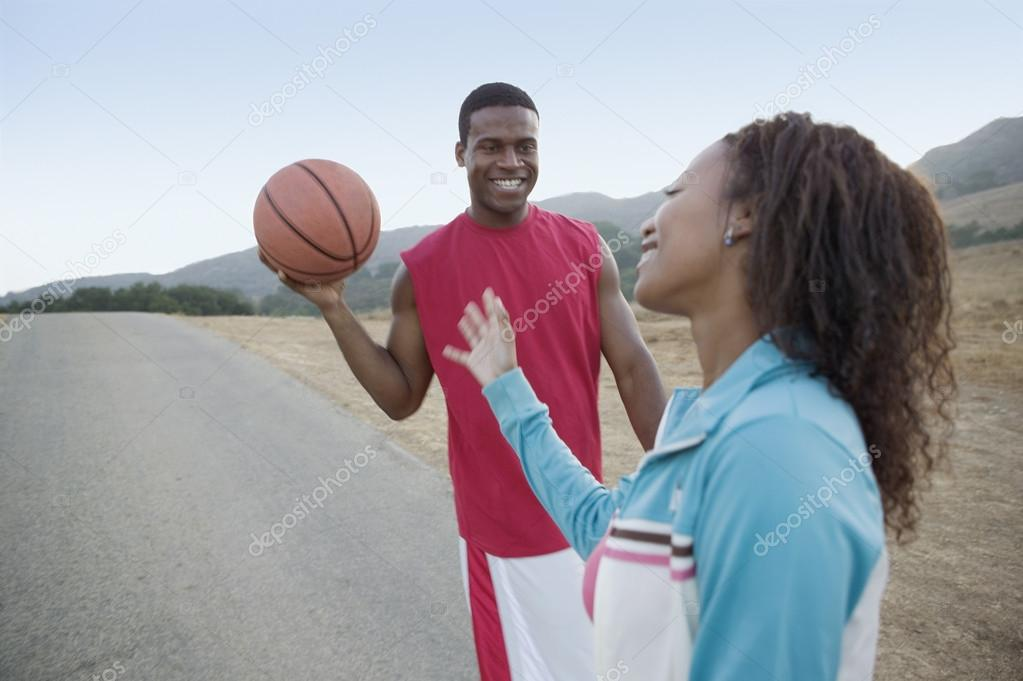 Young couple playing around with basketball