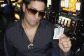 mladý muž, držící své výhry v kasinu