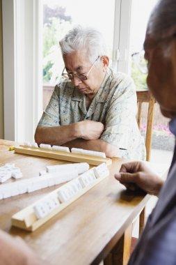 Two elderly men sitting at table playing game