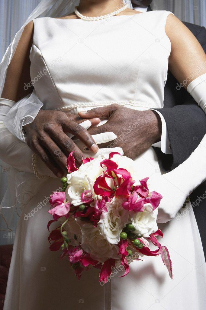 Groom holding his bride's waist