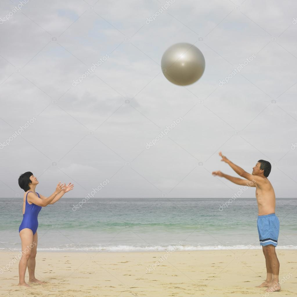 Couple in bathing suits playing with ball at beach