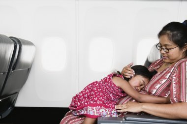 Young girl sleeping on mother's lap on airplane