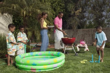 Young family playing outside at barbecue