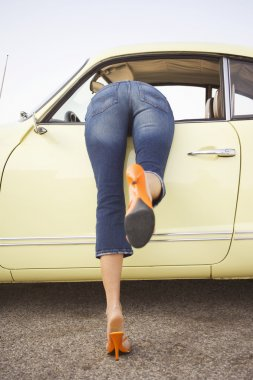 Low section of woman leaning into car