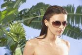 Fotografia Ritratto di donna, occhiali da sole davanti allalbero di banane