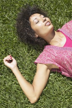 African American woman laying in grass with eyes closed