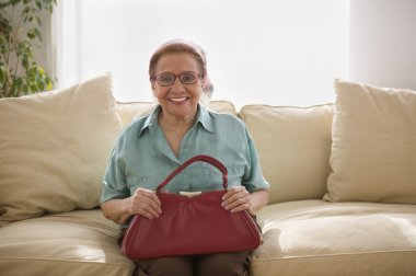 Portrait of elderly woman sitting on couch
