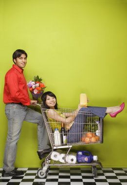 Man pushing woman in shopping cart with groceries