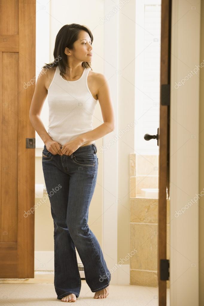 Woman getting dressed in bathroom