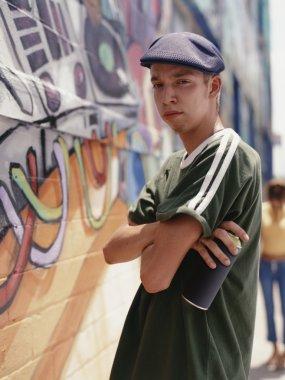 Teenage boy spray painting a wall
