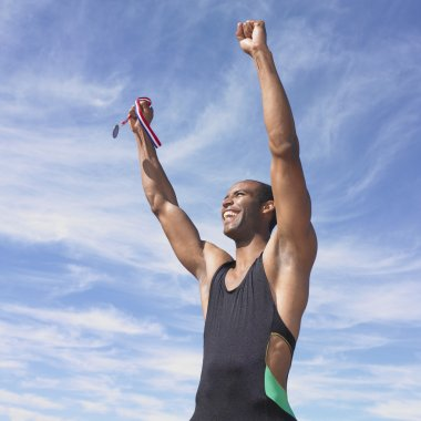 African male athlete cheering while holding medal