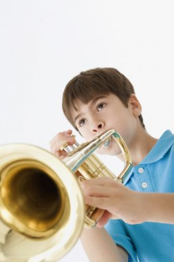Low angle view of a young boy playing the trumpet