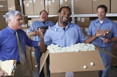 Businessman with male warehouse workers joking around