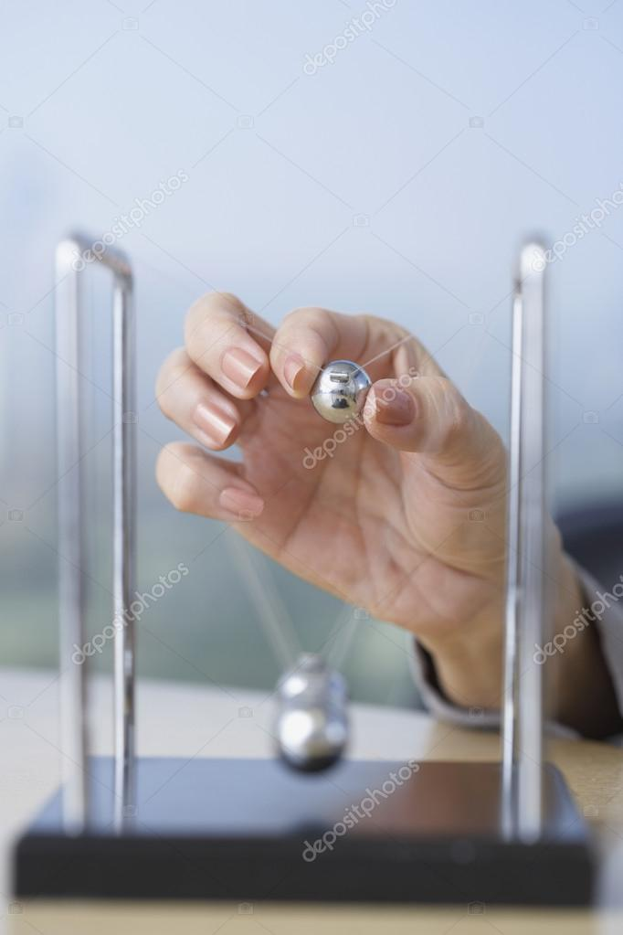 Close up of businesswoman's hand starting perpetual motion device