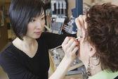 Asijské ženy tvoří umělec výkonu make nad v salonu