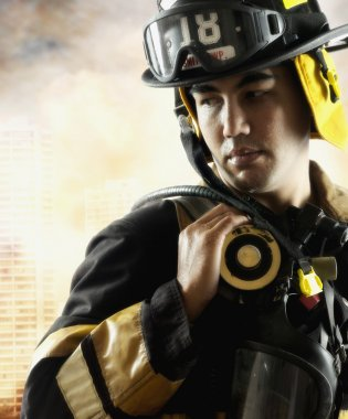 Male fire fighter in front of burning building