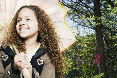 Young African girl holding parasol outdoors
