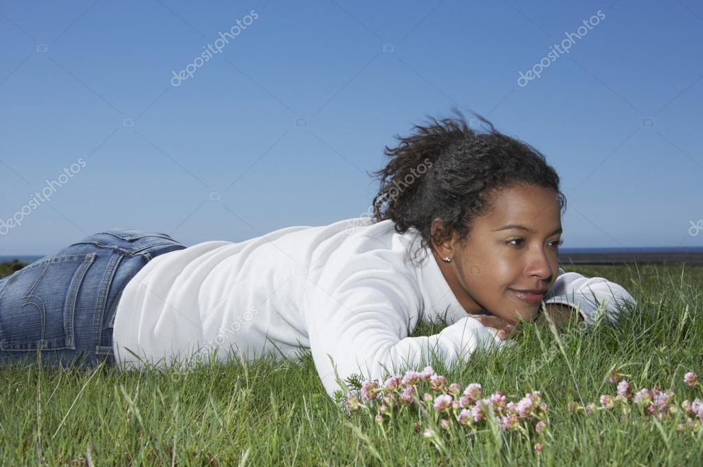 African woman laying in grass smiling