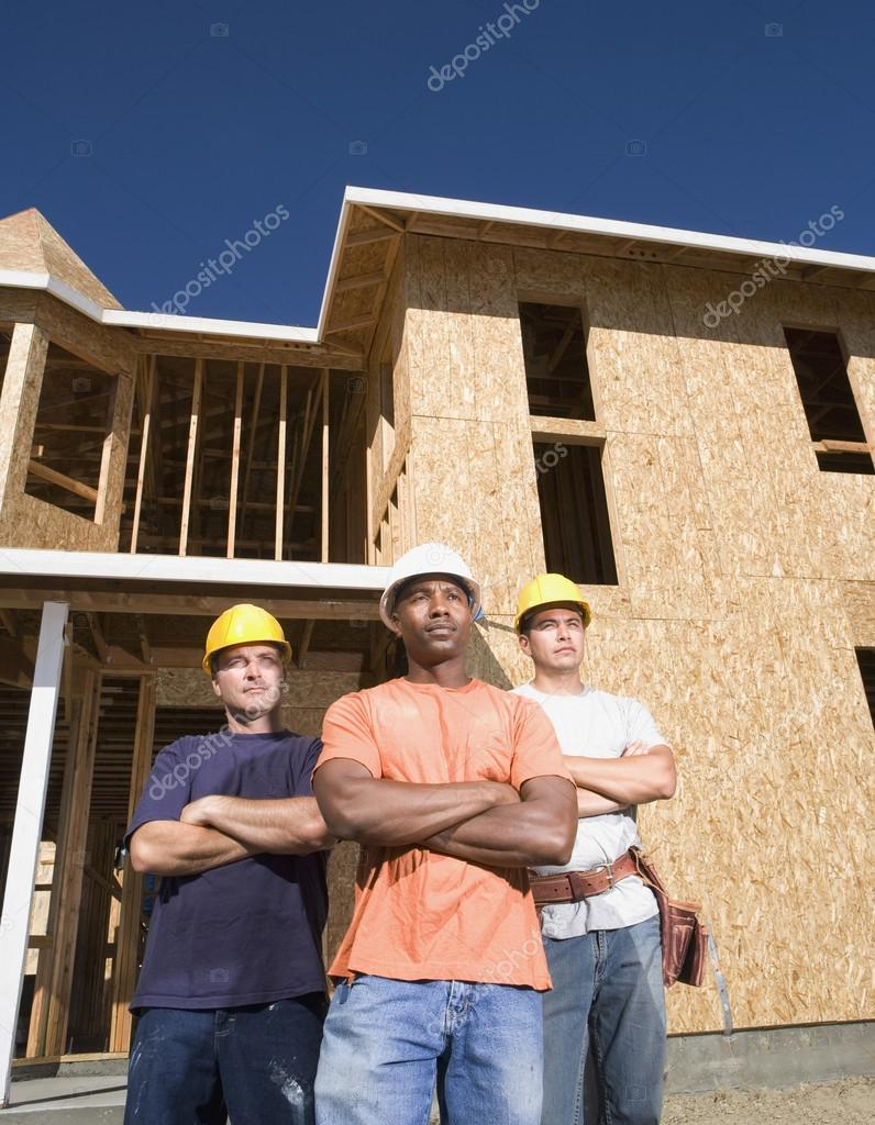 Three construction workers posing outside unfinished building