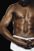 Fotografie Semi-nude African man measuring waist