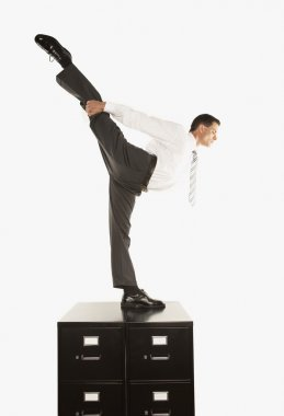 Businessman standing on one leg on filing cabinet