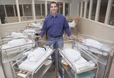 New father with babies in hospital nursery