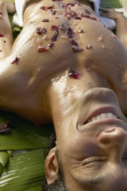 Asian man laying on banana leaves with crushed fruit on bare chest