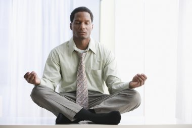 African American businessman meditating on table